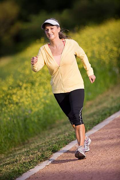 Photo of an older woman walking briskly around a track
