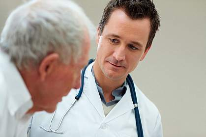 Photo of a physician talking with an older male patient