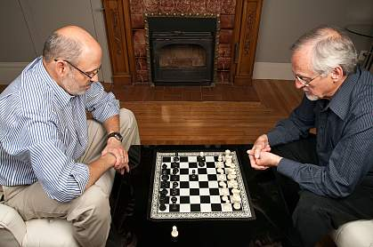 Photo of two older men playing chess
