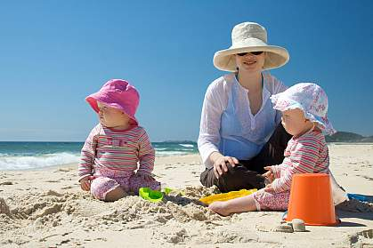 Photo of a woman and a baby wearing sun hats at the beach