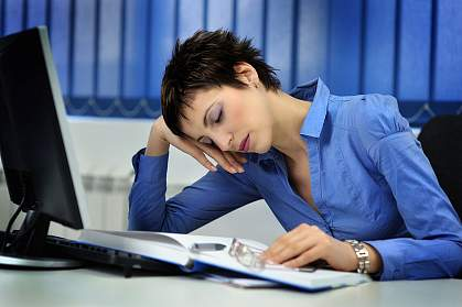 Photo of a woman nodding off at her desk