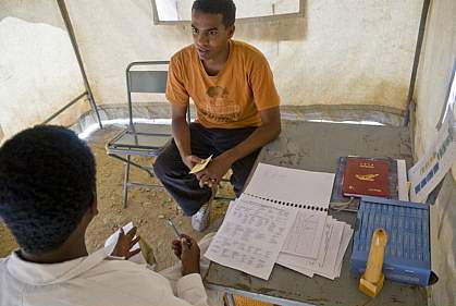 Photo of an young man talking with a doctor in a mobile clinic tent in Africa