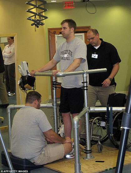 Photo of a standing man supported by hand rails and physical therapists