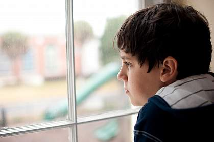 Photo of a young boy looking out a window