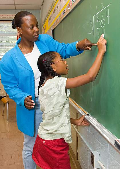 Photo of a teacher and student working on math problems at the chalkboard