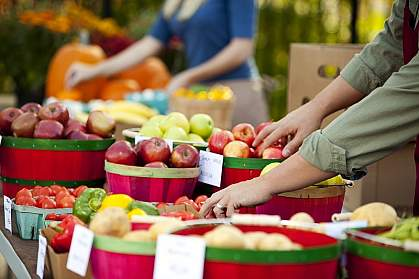 Photo of people reaching for fresh fruit at a farmer's market