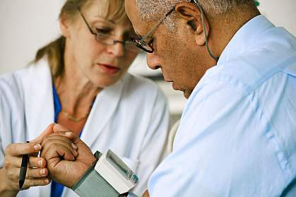 Photo of doctor taking man's blood pressure.