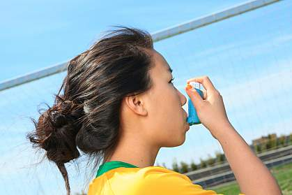 Photo of a girl using an inhaler for asthma