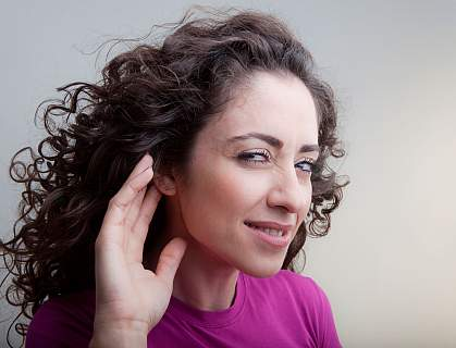 Photo of a young woman cupping her hand to her ear