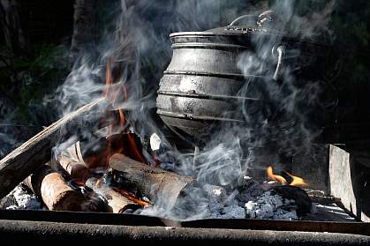 Photo of an iron pot on a smoking fire