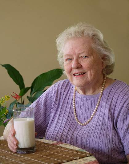 Photo of an older woman with a glass of milk.