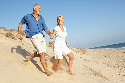 An older couple running down a sand dune.