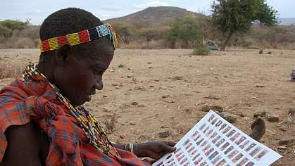 Hadza woman looking at a sheet with photos of other Hadza people.