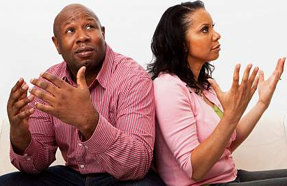 A man and woman throwing their hands up in frustration at each other.