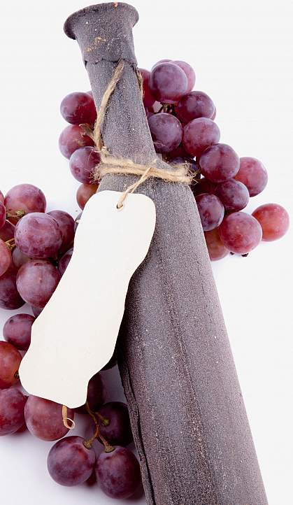 Grapes around a wine bottle.