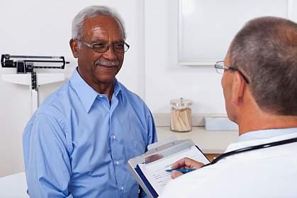 Older man talking to his doctor.