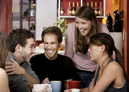 Group of people drinking coffee in a cafe.