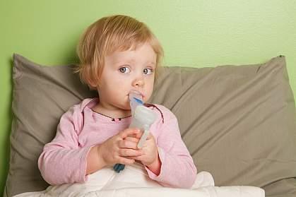 Young girl inhaling mist through a mouthpiece.