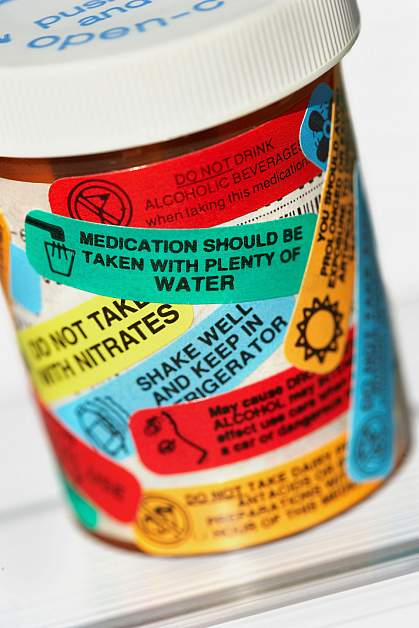 Pill bottle with many warning labels.