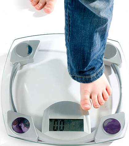 Child's foot stepping onto a scale.