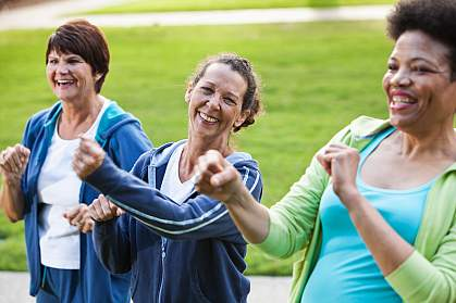 Women in their 50s and 60s exercising outdoors.