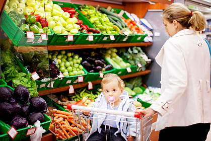 A woman choosing vegetables at a grocery with a baby.