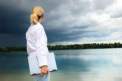 Woman with a laptop looking over a lake as a heavy storm approaches.