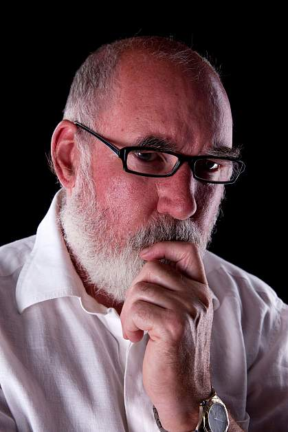 Bearded man in his 60s lost in thought.