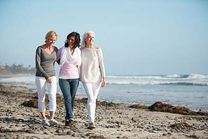 Three mature women walking on a windy beach.
