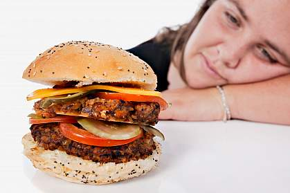Photo of an overweight young woman resting her head on her arm and gazing longingly at a forbidden cheeseburger.