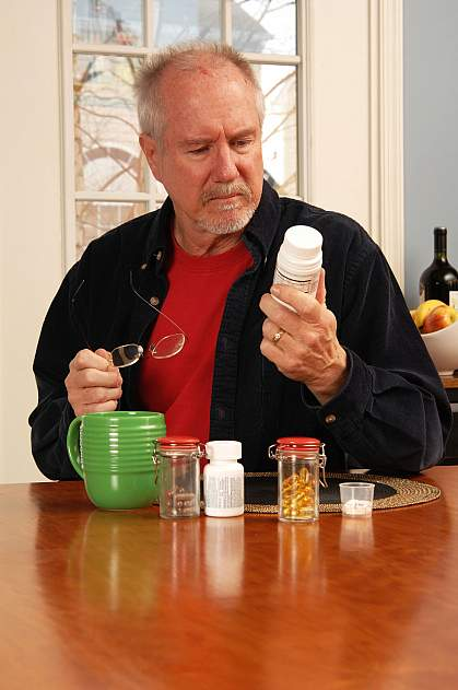 Man reading the label on a vitamin bottle.