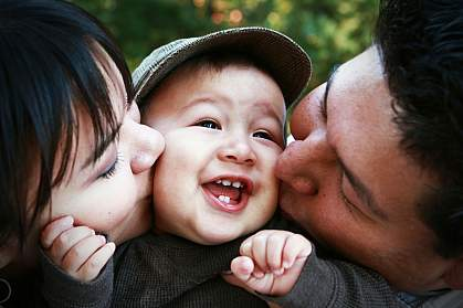 Parents kissing child.