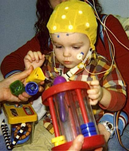 A child wearing a cap to measure brain activity