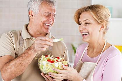 Happy senior couple eating salad in the kitchen.