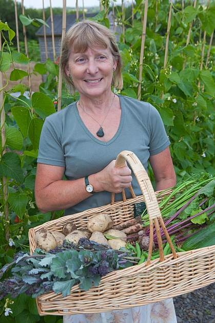 Happy woman with a wicker basket full of fresh vegetables.