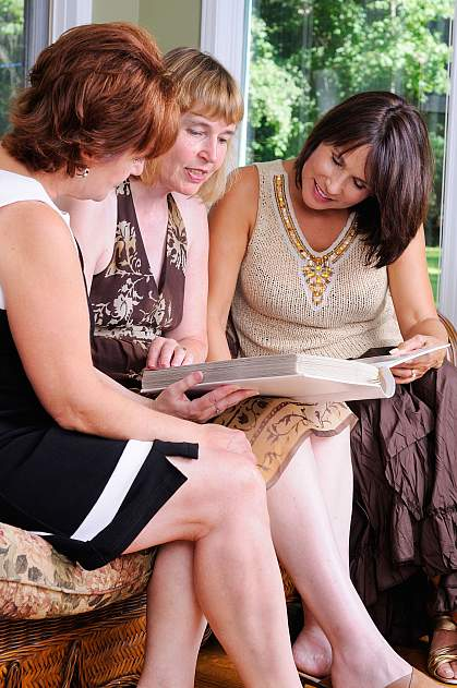 Three middle-aged women looking at a photo album.