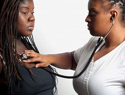 Doctor using a stethoscope to examine an overweight African-American woman.