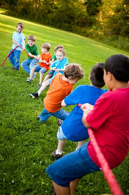 Young boys pulling on a rope in tug of war game.