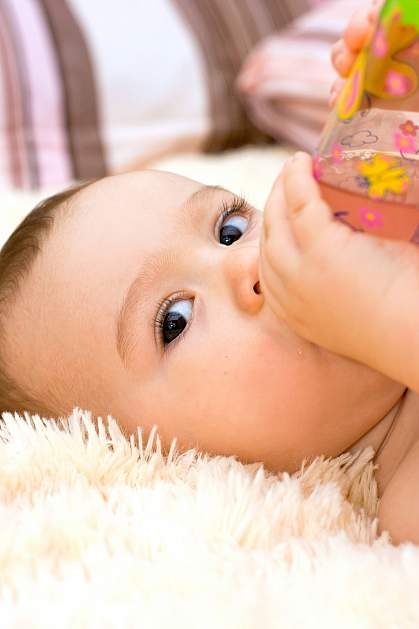 Infant watching someone while drinking from a bottle.