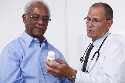 Doctor showing patient prescription bottle.