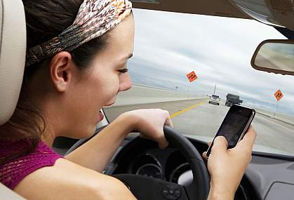 Young woman driving on highway while using smart phone.