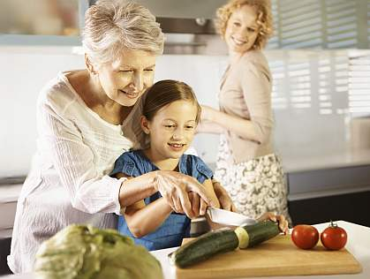 A grandmother helping her granddaughter slice a cucumber as her mother looks on.