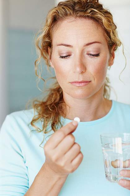 Woman looking pensively at a white pill.