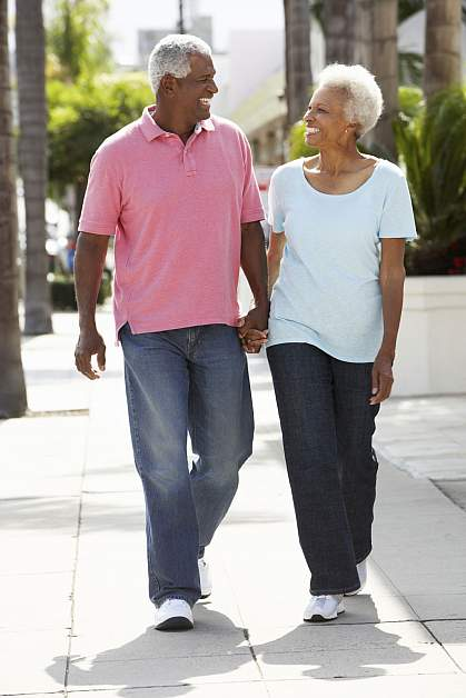 Senior couple walking along the street together.