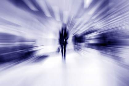 Blurred image of person walking toward camera.