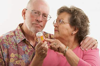 Senior couple reading a prescription bottle.