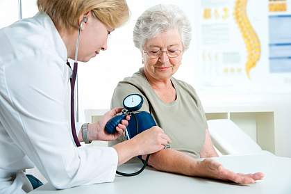 Female doctor measuring blood pressure of senior woman.