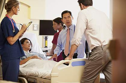 Medical team meeting around female patient in hospital room.