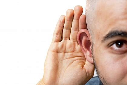 Man cupping his hand to his ear.