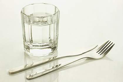 Knife and fork with a glass of water.